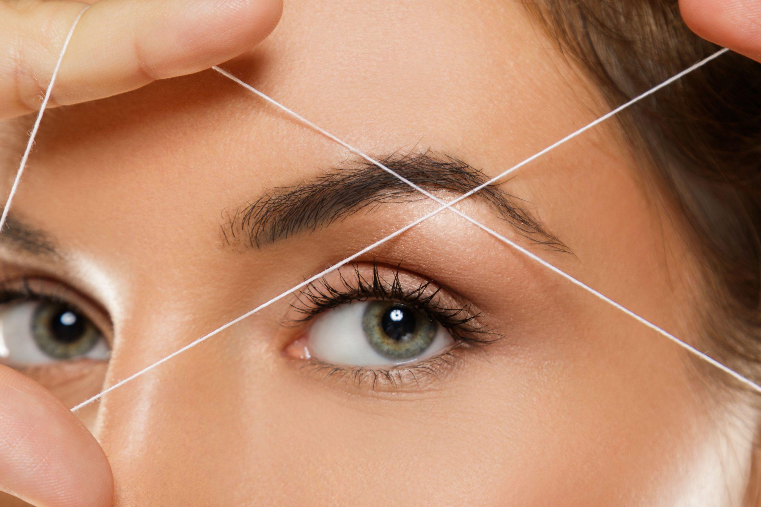 Close-up,Of,Female,Eye,With,A,Thread.,Eyebrow,Threading,-